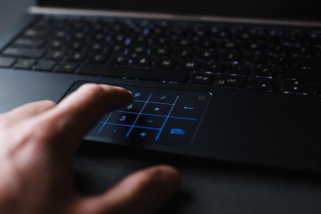 いくつかのデータを計算するラップトップで作業する人の手。ワークスペースのビジネスコンセプト
