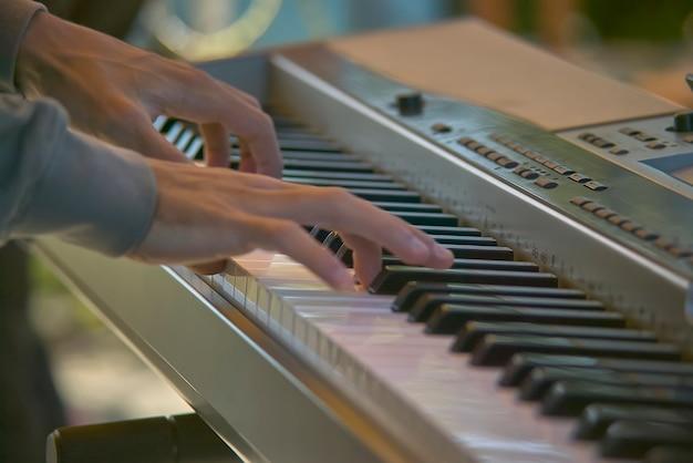 コンサートで演奏中に電子キーボードのキーを押すミュージシャンの手