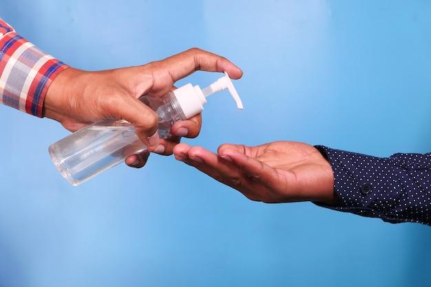 他の人に消毒液を与える人の手