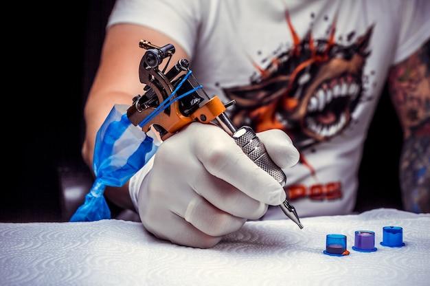 タトゥーマシンを持つプロの彫師の手