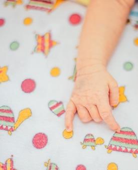 赤ちゃんの毛布の上に横たわっている眠っている新生児の手
