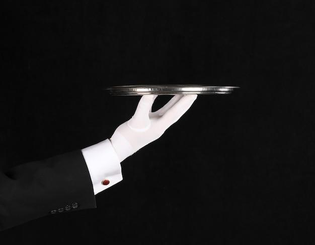검정색 배경에 쟁반이 있는 웨이터의 손