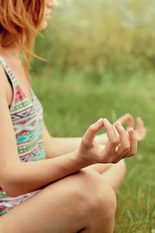 Рука женщины медитирует в позе лотоса, практикующей йогу летом. активный образ жизни. концепция здорового и йоги. фитнес и спорт