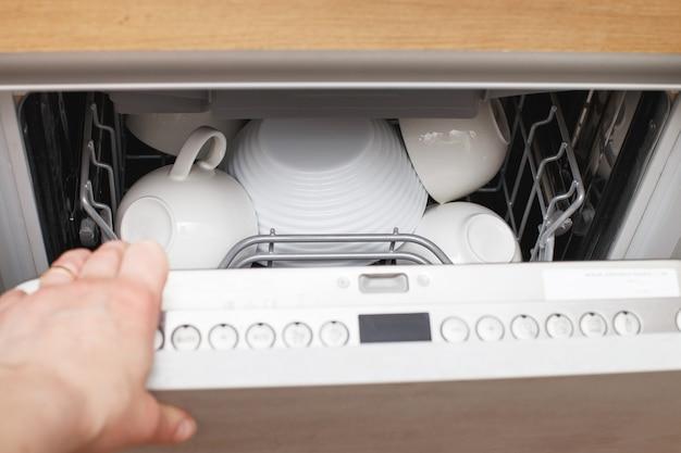 부엌에 깨끗한 접시가 있는 식기 세척기를 여는 여성의 손