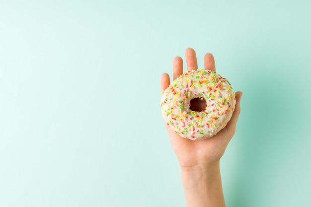 青い表面に艶をかけられたドーナツを持つ女性の手