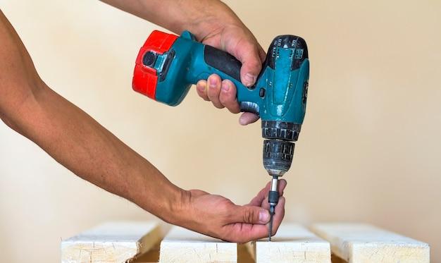 労働者の手は、コードレスドライバーで木の板にネジをねじ込みます。手作りの仕事で男の大工