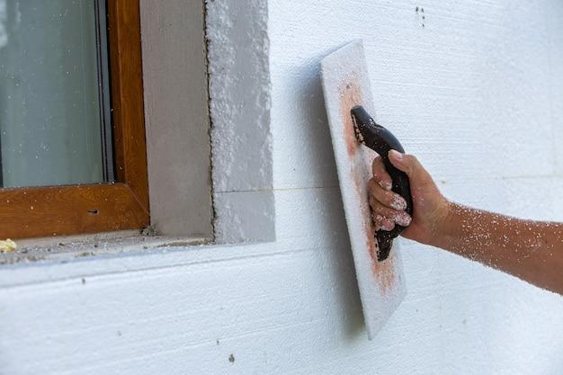 紙やすりで磨き、滑らかにするためのツールを持った労働者の手、そして発泡スチロールの断熱シートで断熱された家の壁の表面さえ。