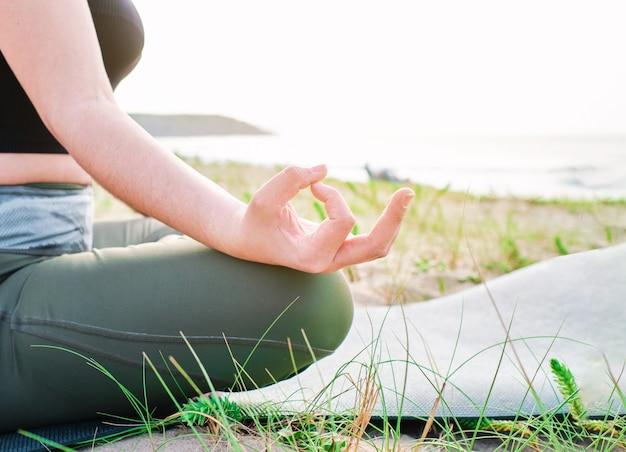 海の前で瞑想に座っている若い女性の手