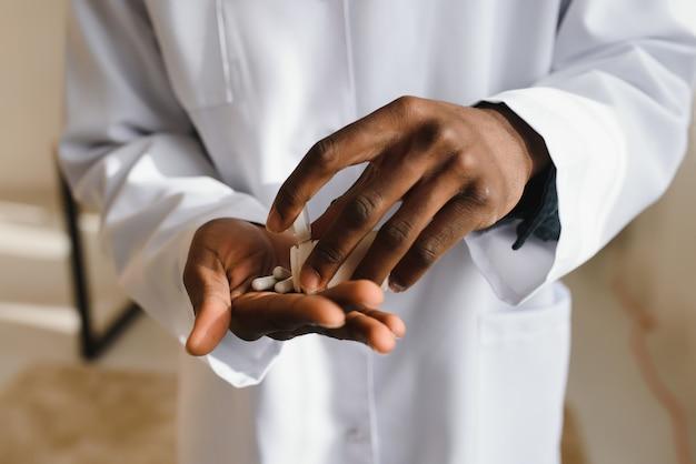 Рука афро-американского врача, держащего таблетки на белом фоне студии, обрезанные