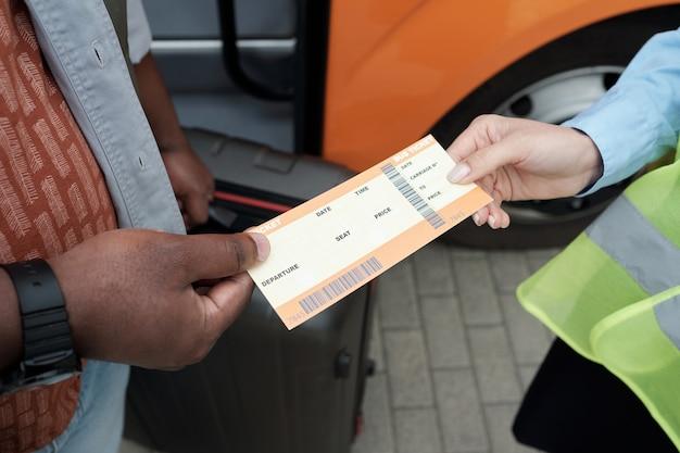 Рука африканского пассажира передает свой билет кондуктору