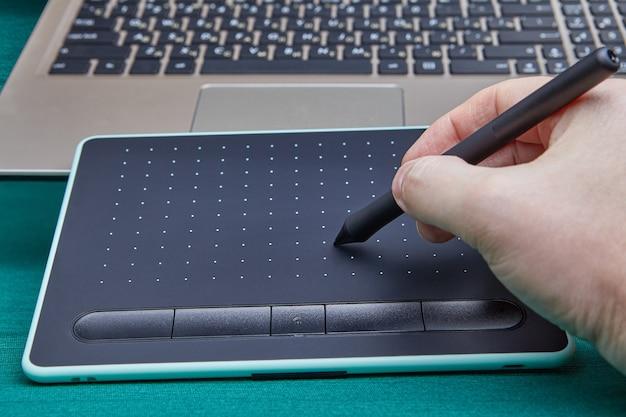 그래픽 편집기 프로그램에서 작업하기 위해 전자 드로잉 보드를 사용하는 스타일러스 펜으로 아티스트의 손.