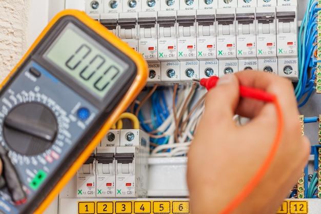 電気でマルチメータプローブを持つ電気技師の手
