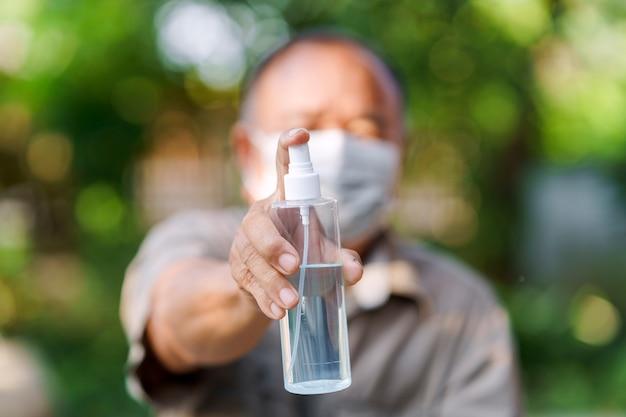 アルコールスプレーボトルを保持しているマスクを身に着けている老人の手衛生コンセプト