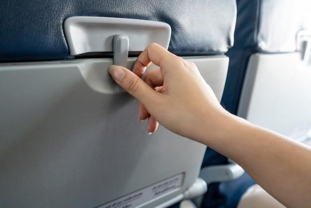 아시아 여성 승객의 손이 저가의 비행기에서 좌석 앞의 트레이를 열려고합니다.