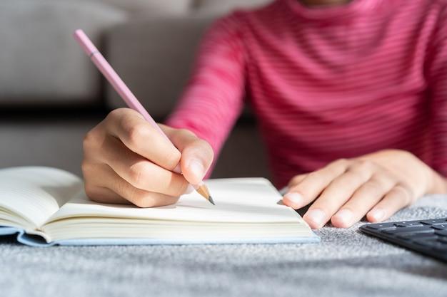 アジアの女の子の手は、リビングルームに座っている間インターネット書き込みノートと宿題を介してオンラインで勉強しています