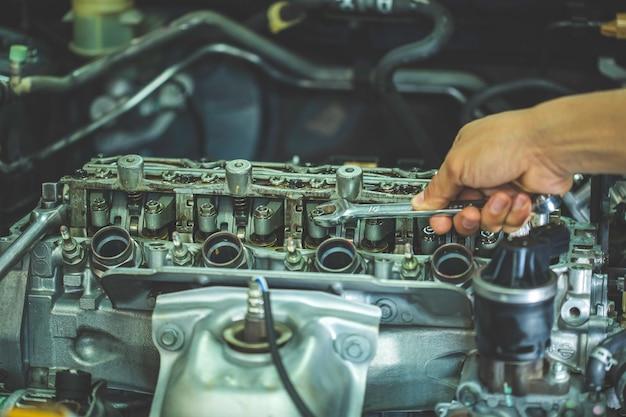 Рука автомеханика с гаечным ключом. концепции инженера и ремонта автомобилей автомобильного двигателя грязные руки, держащие инструменты с помощью