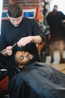Рука парикмахера держит опасную бритву и режет модные полосы на голове клиента