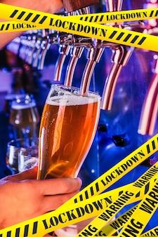 Рука бармена наливает пиво в кран с ограничительными лентами lockdown coronavirus