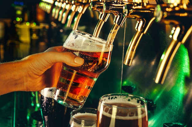 Рука бармена наливает большое светлое пиво в кран. яркий и современный неоновый свет, мужские руки. разлив пива для клиента. вид сбоку молодого бармена, разливающего пиво, стоя у барной стойки.