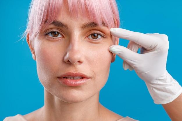 Рука косметолога трогает женское лицо, исследуя его перед инъекцией ботокса