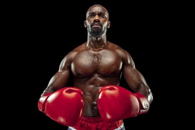 黒の背景にボクサーの手。強さ、攻撃と動きの概念