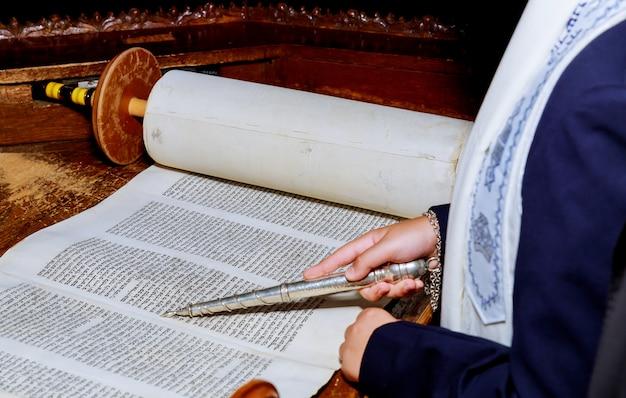バーmitzvahでユダヤ人の律法を読んでいる少年の手