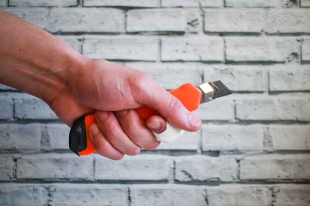Рука строителя с перевязанным пальцем держит резак на фоне кирпичной стены. порез, несчастный случай на работе