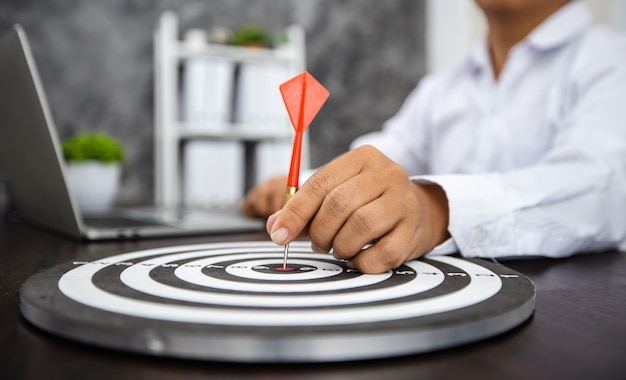 Рука делового человека, держащего дротик на цели с финансовой миллиметровой бумагой с ноутбуком на столе, успешное достижение, концепция успеха и победы