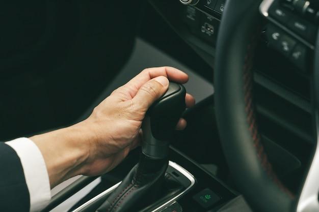 Рука делового человека с часами, держащими водителя, переключая рычаг переключения передач. концепция вождения автомобиля. концепция безопасного вождения.