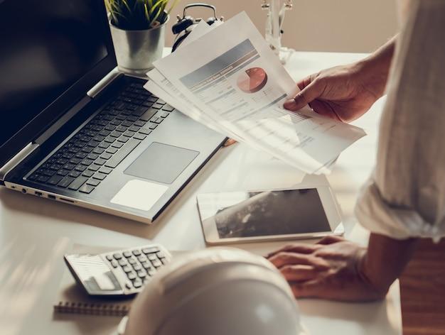 Рука деловых людей рабочий документ о доходах бюджета и планировании проекта строительства