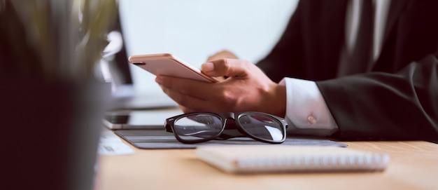顧客と眼鏡に連絡するメッセージを入力すると木製のテーブルでスマートフォンを使用して黒のスーツのビジネスマンの手。