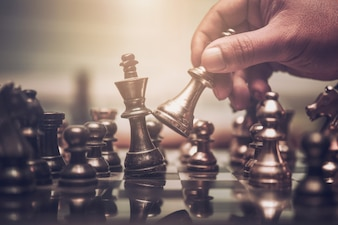 Hand of businessman moving chess figure in competition success play.