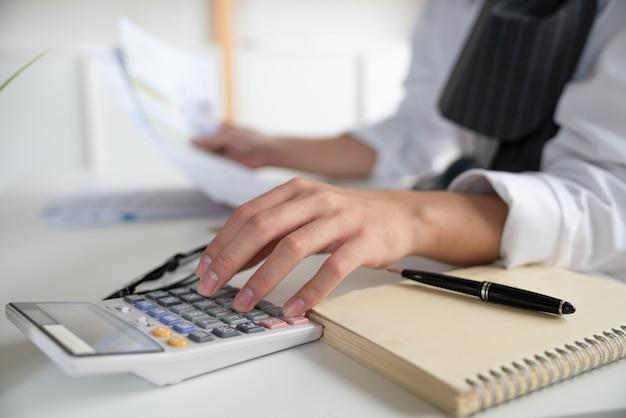 Рука бизнесмена с помощью калькулятора рассчитывает ежемесячный счет расходов