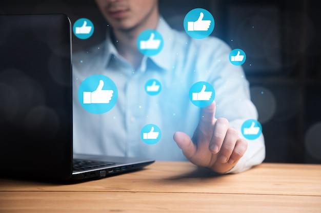 아이콘 소셜 미디어와 소셜 네트워크와 함께 노트북을 사용하는 사업가의 손. 온라인 마케팅 개념