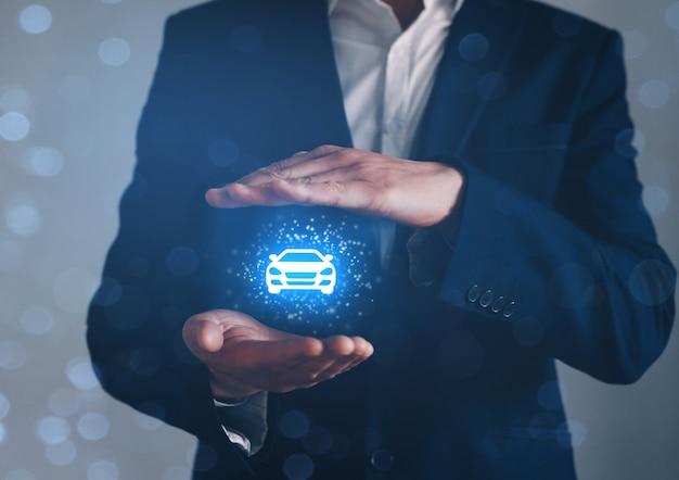 Рука бизнесмена с защитным жестом и значком автомобиля. автострахование или автомобильная концепция.