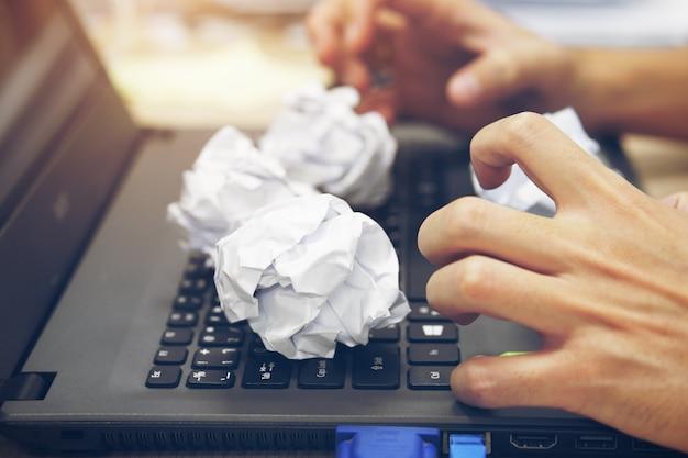 Рука бизнесмена с напряжением чувство на компьютерный ноутбук и мятой бумажный мяч