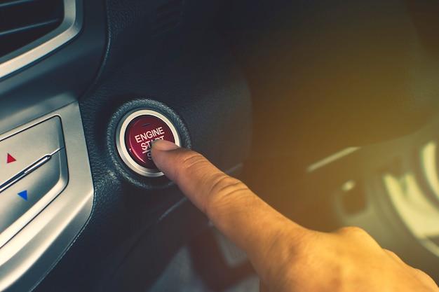車のドライバーの手が高級車のエンジン点火用のエンジンスタート/ストップボタンを押します。