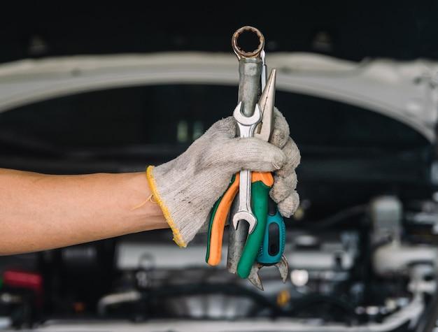Рука автомеханика с ключом автомеханик ремонт, техническое обслуживание и осмотр автомобилей
