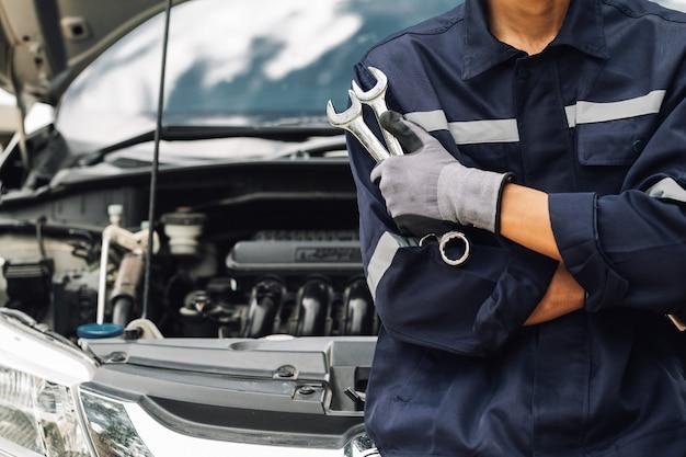 Рука автомеханика с гаечным ключом. авторемонтный гараж. механик работает над двигателем автомобиля в гараже. услуги по ремонту. концепция автосервиса и автосервиса.