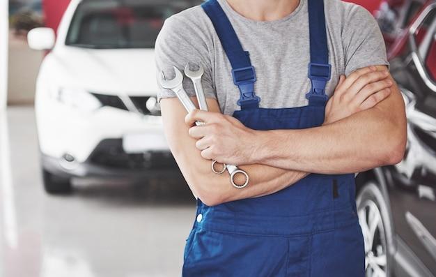 렌치와 자동차 정비사의 손입니다. 자동차 수리 차고.