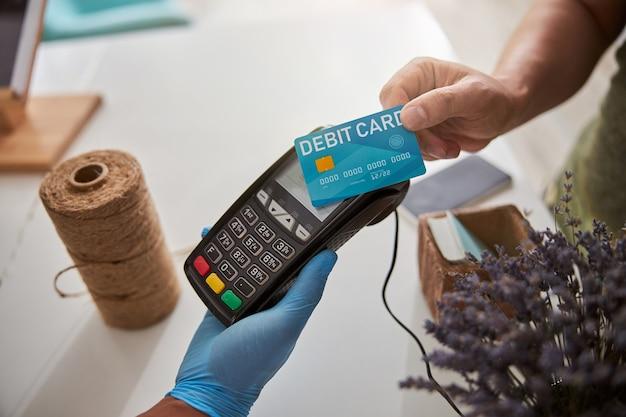フラワーストアのカウンターにあるpos端末に銀行カードを押す白人男性の手