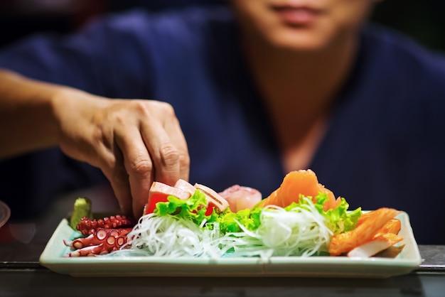 Рука шеф-повара изготовление суши на суши-баре