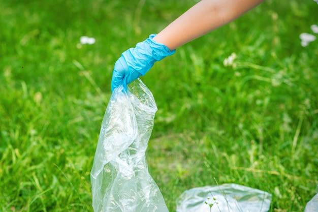 Рука ребенка очищает парк от пластикового мусора, лежащего на зеленой траве