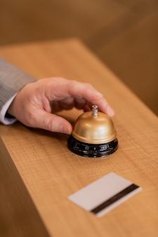 Рука современного бизнесмена над кнопкой кольца на деревянной стойке регистрации, чтобы вызвать портье отеля