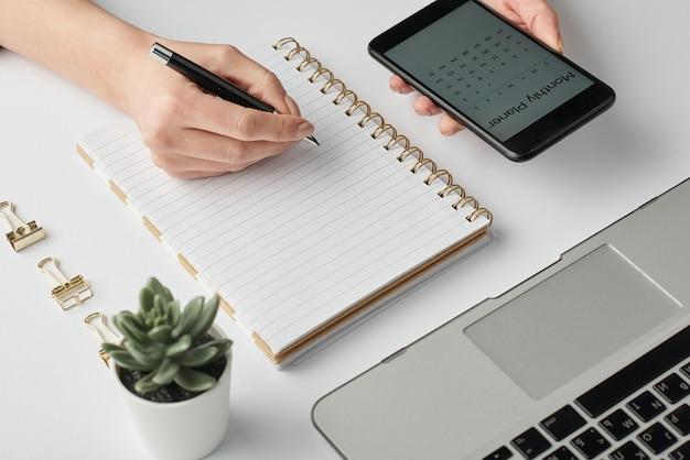 Рука современной бизнес-леди с ручкой над пустой страницей записной книжки во время планирования работы за столом