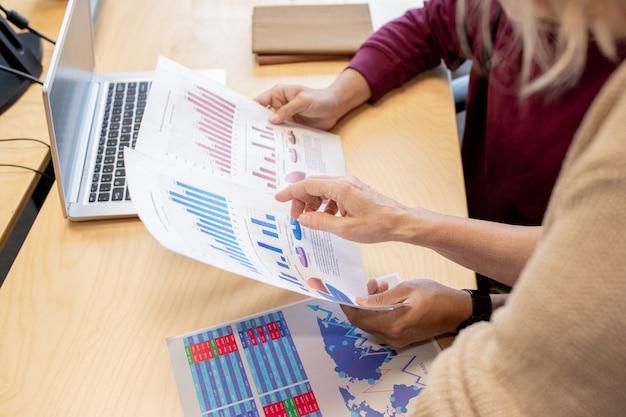 책상에서 차트와 그래프를 논의하면서 동료가 보유한 재정 서류 중 하나를 가리키는 현대 여성 브로커의 손
