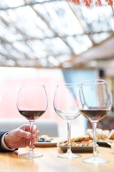 Рука современного эксперта по виноделию берет один из бокалов с каберне перед проверкой его качества