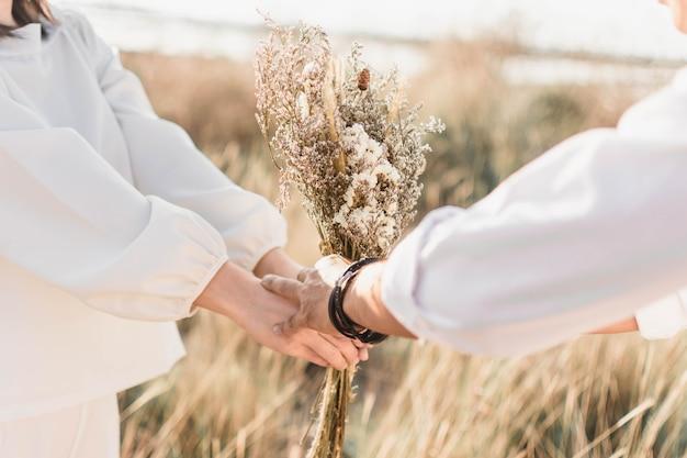 Рука пара любви с цветком и природа фон.