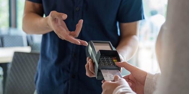 Nfc 기술이 적용된 비접촉 신용 카드로 결제하는 고객의 손. 신용 카드를 들고 있는 여성이 있는 바 카운터에 신용 카드 판독기가 있는 바텐더. 손에 초점을 맞춥니다.