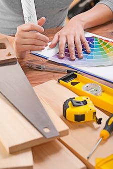 Рука дизайнера на цветовой палитре рядом с другими инструментами